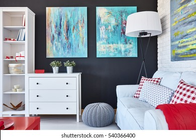 Creatively designed living room with sofa, chest of drawers, cupboard and painting