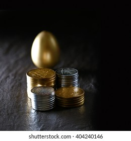 Creatively lit concept image for pension fund, investments, and savings. Gold and silver coins with a golden egg against a dark background on oiled slate. Copy space.