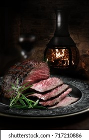 Creatively lit, fresh British roast beef plated and carved against a dark, rustic and cosy background with rosemary herb garnish. Generous accommodation for copy space.