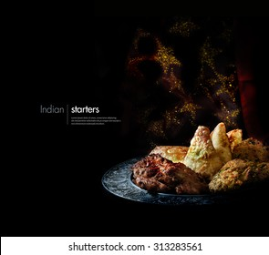 Creatively lit platter of traditional Indian cuisine starters and appetizers against a sparkling Indian background with accommodation for copy space.