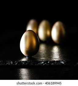 Creatively lit and positioned golden eggs against a black background on oiled slate. Concept image for investments, savings and pensions. Generous accommodation for copy space.