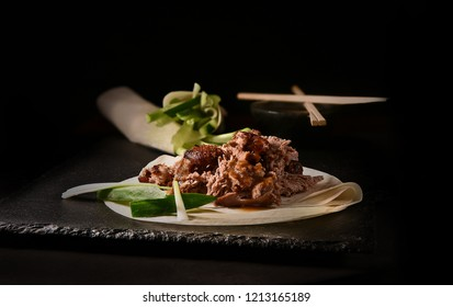 Creatively lit succulent classic Chinese shredded Peking duck with Hoisin sauce and flour pancakes with sliced scallions and cucumber garnish. Copy space.