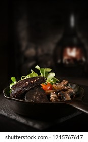 Creatively lit traditional black pudding slices with garlic portobello mushrooms and fresh green salad shot against a dark, rustic background with generous accommodation for copy space.