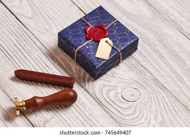 Creatively wrapped and decorated christmas present in box and wax seal stamp on white wooden background