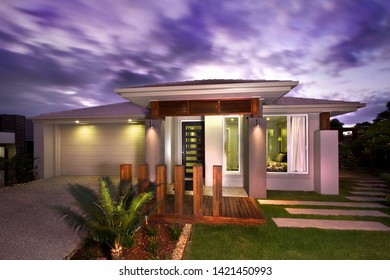 Creatively-designed house entrance with glass windows, wooden plank flooring, lamps, wooden pillars, and grass
