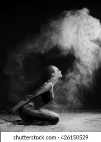 Creativity concept. Mind-blowing portrait of beautiful young woman in cloud made of flour. Black and white studio shot