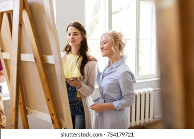 creativity, education and people concept - artists or student girl with palette and teacher discussing painting on easel at art school studio