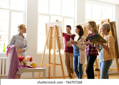 creativity, education and people concept - drawing teacher showing still life composition to group of artists or students at art school studio