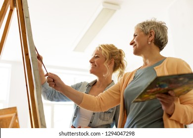 creativity, education and people concept - female artists or students with brushes and palettes painting on easel at art school studio