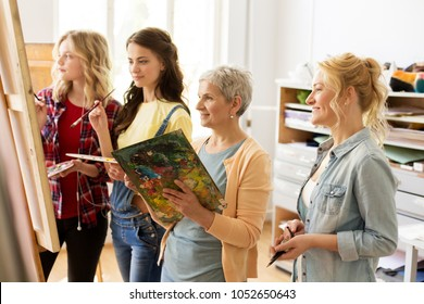 creativity, education and people concept - group of female artists or students with brushes and palettes and teacher painting on easel at art school studio
