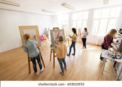 creativity, education and people concept - group of woman artists or students with brushes and palettes painting and drawing still life picture on easels at art school studio