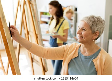 creativity, education and people concept - senior woman drawing with pencil on easel at art school studio