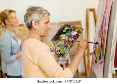 creativity, education and people concept - senior woman with brush and palette painting still life picture on easel at art school studio