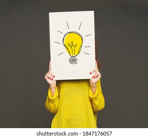 Creativity and innovations concept. Unrecognizable young woman holding poster with drawing of light bulb in front of her face, grey background. Best ideas and development strategies