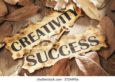 Creativity is key to success concept using words printed on burnt paper and related objects, surrounded with dry leaf