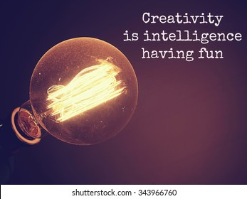 Creativity Typographic quote of Creativity  is intelligence having fun ,on dark background with retro light bulb is glowing. Message for your design or inspirational poster.