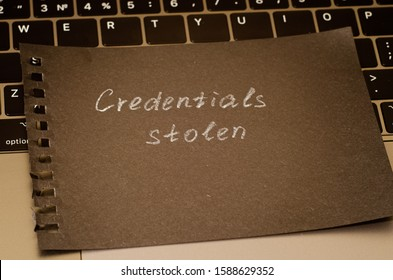Credentials stolen phrase written in white pencil on a piece of black paper, lies on a laptop keyboard. Information Security Weakness Concept.