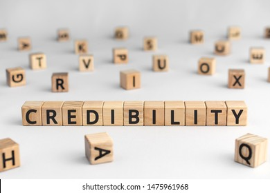 Credibility - word from wooden blocks with letters, reliability trustworthiness believability concept, random letters around, white  background