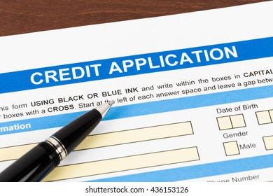Credit application form with pen; document is mock-up