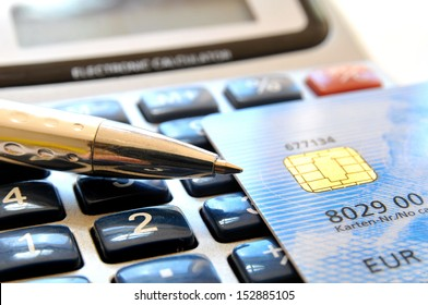 Credit card and ball pen on a calculator