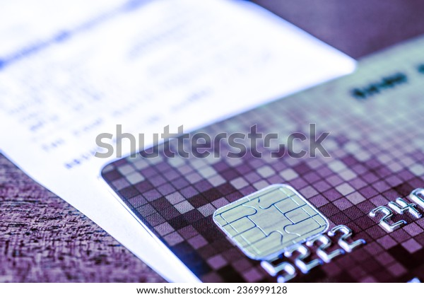 Credit card and check from shopping on the table, focus on the microchip of the card. In blue tone