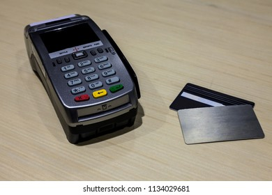 Credit Card Debit Card Reader Machine/Credit Card Debit Card Terminal EDC on wooden table with credit cards lay on table by side