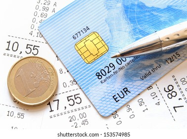 Credit Card and Euro coin on top of supermarket receipts