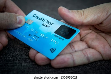 Credit card has built-in fingerprint scanner. Illustration of biometric payment security. One male hand is holding blue card and other touching scanner with thumb. Verifying by pressing. Identity