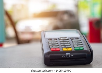 Credit card machine with car refueling petrol at gasoline station in background.Credit card reader payment, buy and sell products & service Credit Card Terminal or EDC on cashier table.