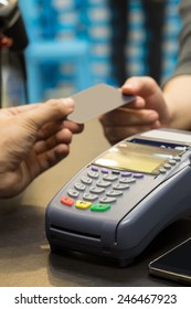 Credit Card Machine On The Table with Hand Paying by Credit Card