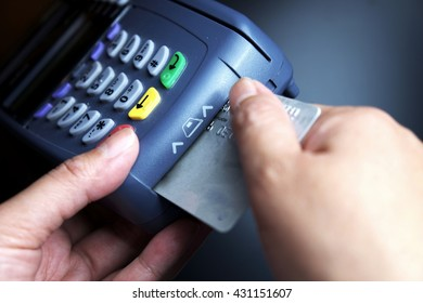 Credit card machine/payment terminal insulated with card on black background. Focus on machine and card. Dark tone.