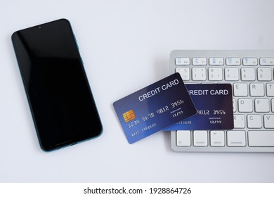 Credit card on computer keyboard with smartphone on white desk. Concept of Online shopping and payment. Top view.