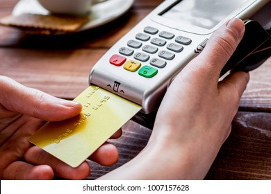 Credit card payment for business lunch in cafe on wooden backgro