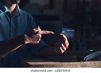 Credit card payment,  man show credit card in hand and reader machine on desk