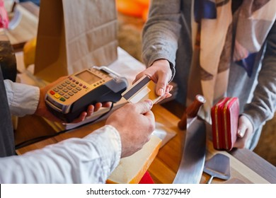 Credit card payment service. Customer paying for order of cheese in grocery shop.