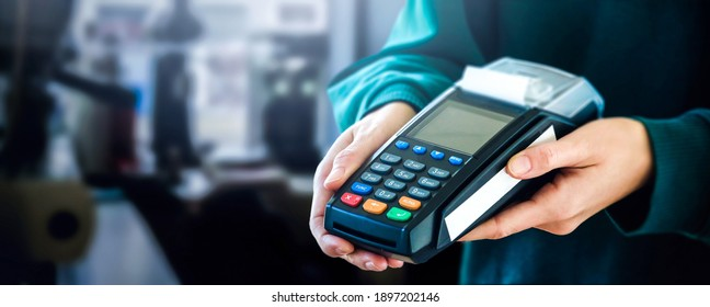 Credit Card payment Terminal in woman hands on blur coffee shop background. Close up view. Buy and sell products concept.