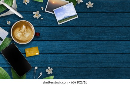 Credit card payment for travel, food and drink. Top view Credit card, Seascape photos,Airplane, Smartphone,Coffee cup , Sneakers and Plumeria flower on blue wooden table. Commerce and travel concept.