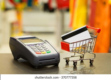 Credit Card In Shopping Cart With Credit Card Machine In Store : Selective Focus On Credit Card