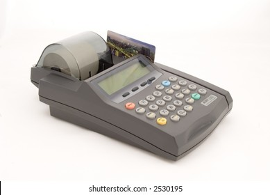 A credit card sits ready to be swiped in a credit card machine, on white, full view