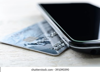 Credit card and smartphone lying on a white wooden table