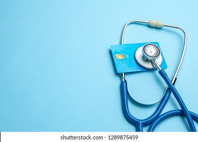 Credit card with stethoscope on blue background. The concept of medical strechevka or expensive medicine, doctors salary. Copy space for text
