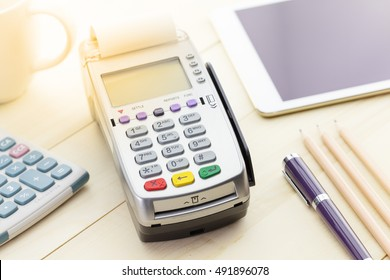 Credit Card Terminal or EDC on cashier wooden table in the store with calculator, pen, pencil, digital tablet and glasses on wooden background with copy space.