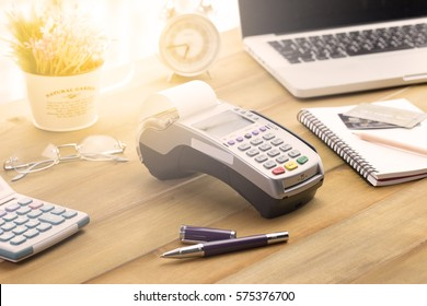 Credit Card Terminal or EDC on cashier wooden table in the store with credit card, pen, laptop and glasses on background.