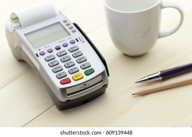Credit Card Terminal or EDC on cashier wooden table in the store with japanese bank notes, pen, pencil and calculator.