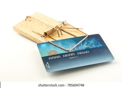 Credit card trapped in a mousetrap. Metaphor of the debt trap. On white background. Studio Shot.