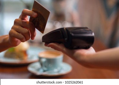 Credit card usage. Moment of payment with a credit card hold by female hand through terminal which carried by another hand