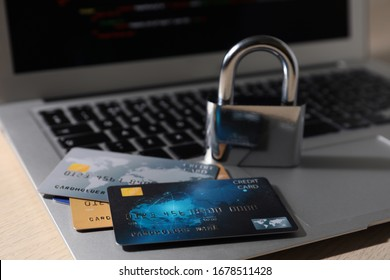 Credit cards, lock and laptop on table, closeup. Cyber crime