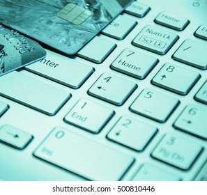 Credit cards on a laptop keyboard. On line shopping, e-commerce and internet purchase concept. Selective focus. Toned.