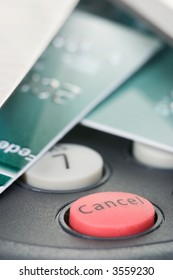 Credit cards on pin pad card reader out of focus with attention on red cancel button