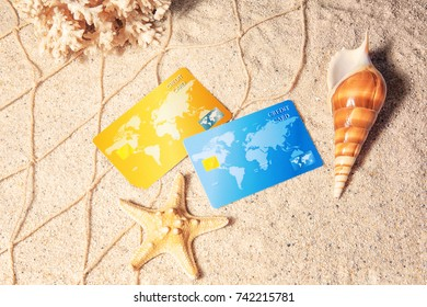 Credit cards with shell and starfish on sand